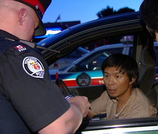 A polícia de Toronto interroga Lu Ping sobre a entrega do boletim informativo do Crescent Chau sobre o Falun Dafa em 30 de junho de 2007 na loja Asian Farm, no nordeste de Toronto (NTDTV)