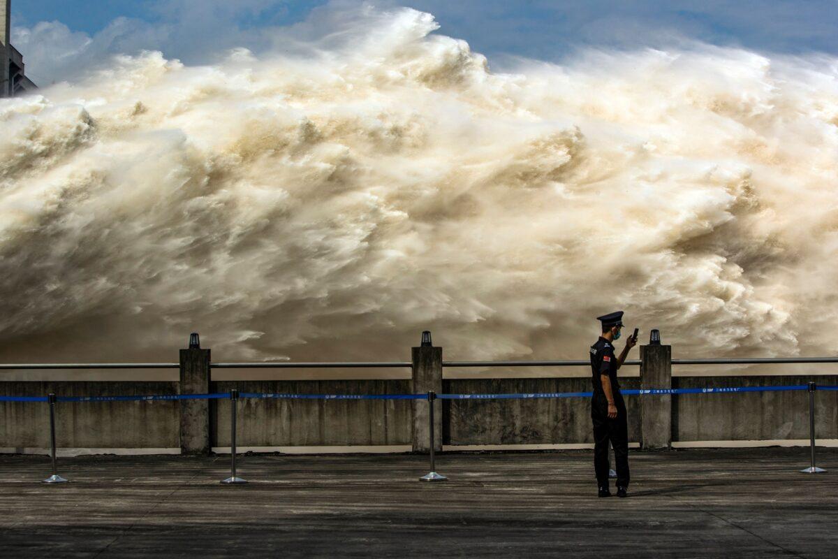 Um guarda de segurança olha para seu telefone celular enquanto a água é liberada da Barragem das Três Gargantas, um projeto hidroelétrico gigante no rio Yangtze, para aliviar a pressão das enchentes em Yichang, província de Hubei, no centro da China, em 19 Julho de 2020 (STR / AFP via Getty Images)