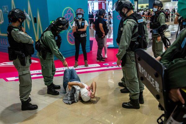 Um policial de choque aponta para uma mulher no chão após ser revistada durante uma manifestação em um shopping center em Hong Kong em 6 de julho de 2020 (Isaac Lawrence / AFP via Getty Images)