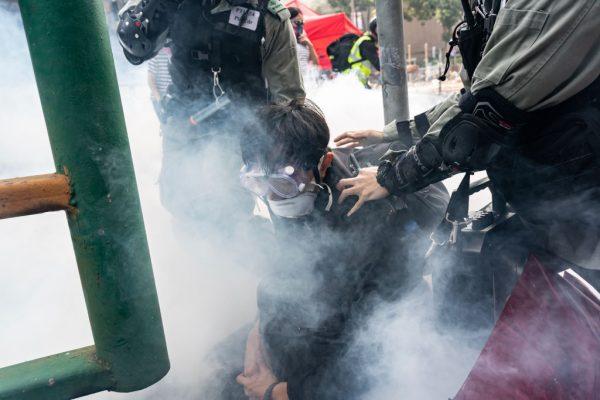 Um manifestante é detido pela polícia enquanto tentava escapar da Universidade Politécnica de Hong Kong, em 18 de novembro de 2019, em Hong Kong, China (Anthony Kwan / Getty Images)