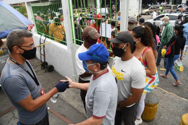 Os compradores usando máscaras faciais desinfetam as mãos, mostrando uma identificação na entrada do mercado municipal de Mesuca, em Petare, em 1º de agosto de 2020 em Caracas, Venezuela (Foto de Carlos Becerra / Getty Images)