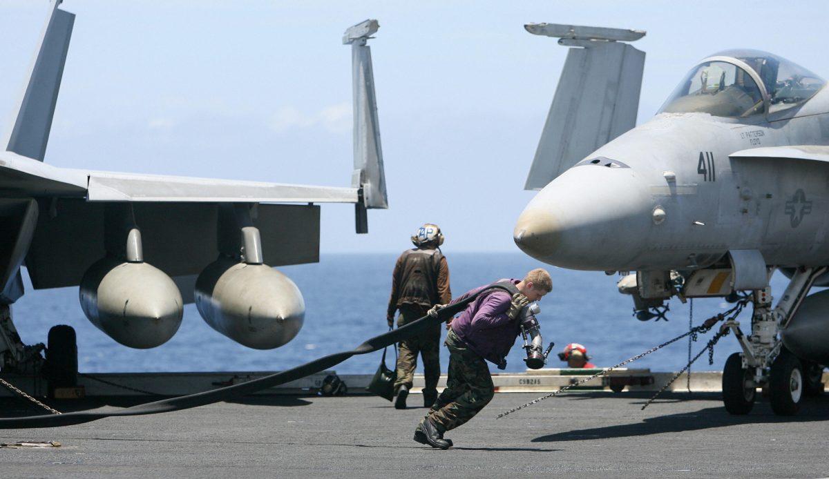 Um tripulante da Marinha dos EUA puxa um tubo de combustível pelo convés do porta-aviões USS Kitty Hawk (CV63) na Baía de Bengala, durante o exercício Malabar em 7 de setembro de 2007 (DESHAKALYAN CHOWDHURY / AFP via Getty Images )