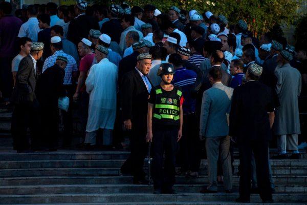 Uma foto tirada em 26 de junho de 2017 mostra um policial montando guarda enquanto os uigures chegam para a oração matinal de Eid al-Fitr na mesquita Id Kah em Kashgar, na região autônoma uigur de Xinjiang na China (JOHANNES EISELE / AFP / Getty Images)