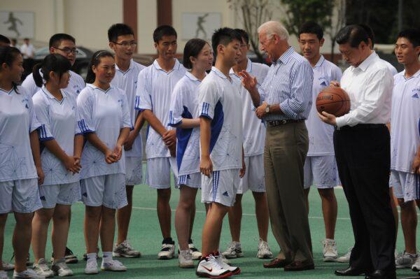 O então vice-presidente dos Estados Unidos, Joe Biden (centro-direita), fala com um estudante enquanto o vice-presidente chinês Xi Jinping (direita) assina uma bola de basquete na Dujiangyan Qingchengshan High School, nos arredores de Chengdu, no Província de Sichuan no sudoeste (China), em 21 de agosto de 2011 (PETER PARKS / AFP via Getty Images)