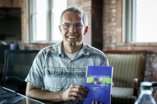 Dr. Brad Roberts, médico do pronto-socorro, mostra um novo livro escrito por especialistas médicos, em Pueblo, Colorado, em 29 de setembro de 2020 (Charlotte Cuthbertson / The Epoch Times)