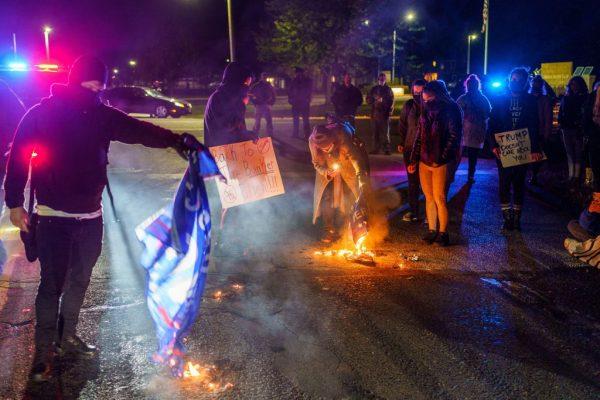Manifestantes anti-Trump queimam as bandeiras da campanha de Trump em frente ao Aeroporto Duluth, 30 de setembro de 2020 (KEREM YUCEL / AFP via Getty Images)