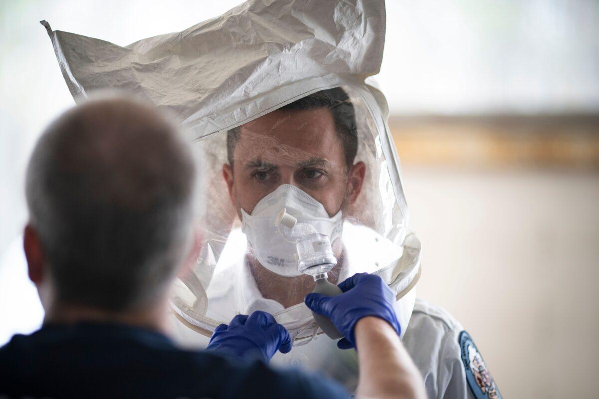 Um paramédico com o Corpo de Bombeiros do Condado de Anne Arundel testa sua máscara N-95 no início de seu turno de 24 horas em Glen Burnie, Maryland, em 9 de abril de 2020 (Alex Edelman / AFP via Getty Images)