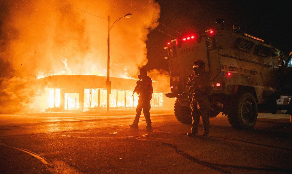 Uma viatura policial blindada em um cruzamento enquanto um prédio está pegando fogo devido aos incêndios causados pelos manifestantes em Kenosha, Wisconsin, em 24 de agosto de 2020 (Brandon Bell / Getty Images)