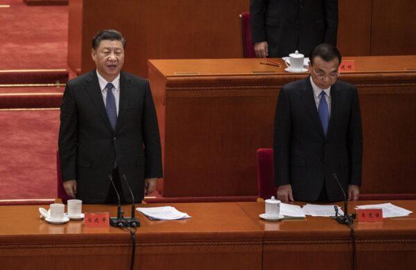 O líder chinês Xi Jinping (à esquerda) e o primeiro-ministro Li Keqiang cantam o hino nacional em uma cerimônia que marca o 70º aniversário da entrada da China na Guerra da Coréia, no Grande Salão do Povo, em Pequim, China, em 23 de outubro de 2020 (Kevin Frayer / Getty Images)