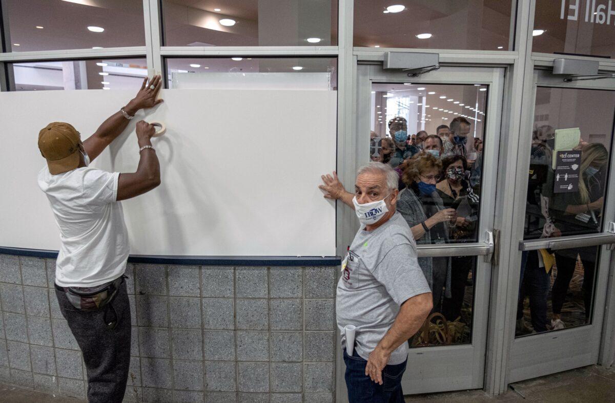 Eleitores cobrem as janelas para que os observadores não possam ver a área de contagem de votos no Centro TCF, onde as cédulas são contadas no centro de Detroit, 4 de novembro de 2020 (Seth Herald / AFP via Getty Images)