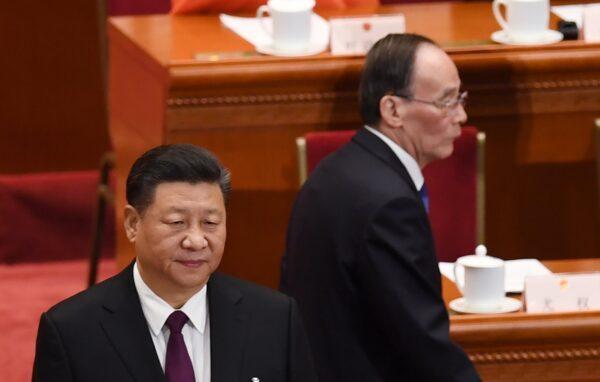 O líder da China Xi Jinping (à esquerda) se levanta enquanto Wang Qishan (à direita), ex-secretário da Comissão Central de Inspeção Disciplinar, chega à primeira sessão do PCC no 13º Congresso Nacional do Povo, em Pequim, em 17 de março de 2018 (GREG BAKER / AFP por meio do Getty Images)