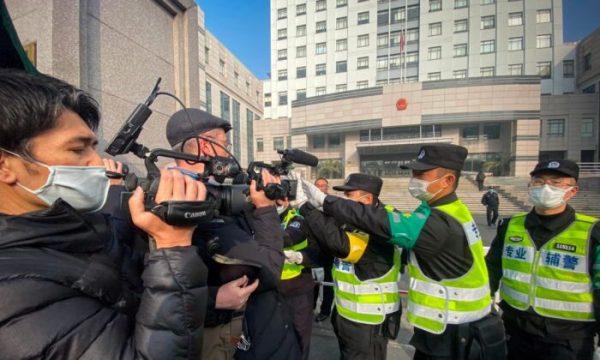 A polícia tenta impedir que jornalistas gravem imagens do lado de fora do Tribunal Popular do Novo Distrito de Pudong, em Xangai, China, em 28 de dezembro de 2020 (Leo Ramirez / AFP via Getty Images)