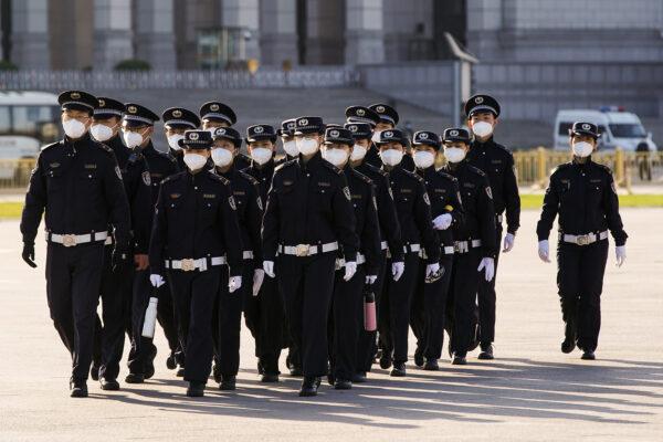 Policiais chineses mascarados marcham pela Praça Tiananmen em Pequim, China, em 4 de abril de 2020 (Lintao Zhang / Getty Images)