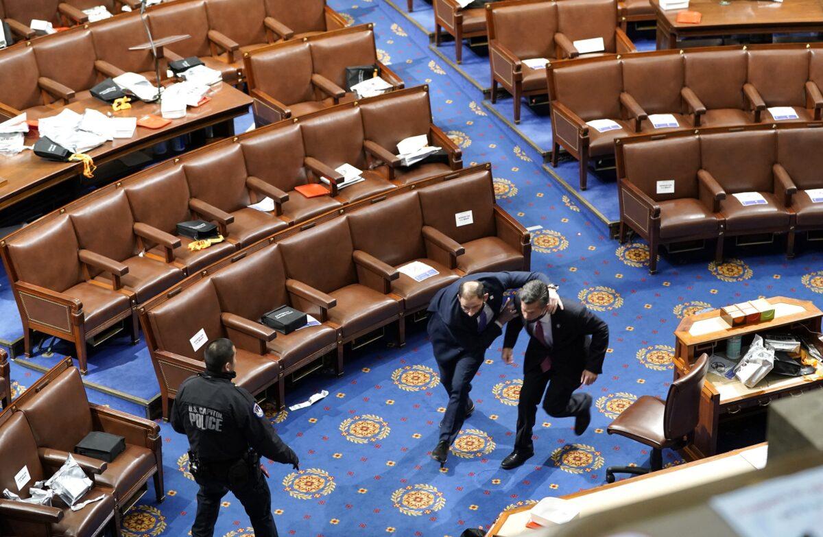 Membros do Congresso correm para se proteger enquanto os manifestantes tentam entrar na Câmara dos Representantes durante uma sessão conjunta do Congresso em Washington em 6 de janeiro de 2021 (Drew Angerer / Getty Images)