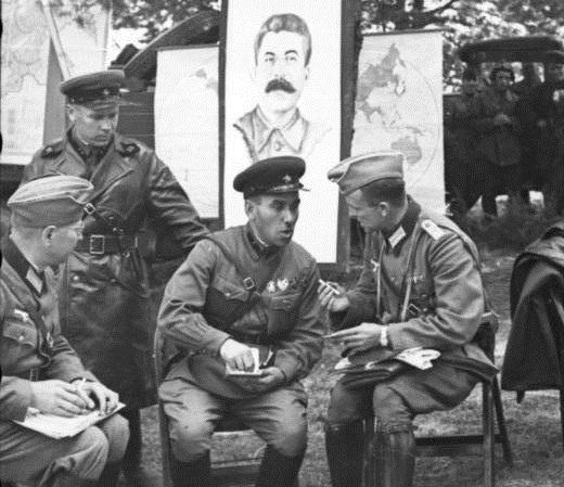 Oficiais soviéticos e alemães socializando durante uma celebração de vitória na Polônia em 22 de setembro de 1939. Um pôster de Stalin está pendurado atrás deles (Bundesarchiv, Bild/CC-BY-SA 3.0)