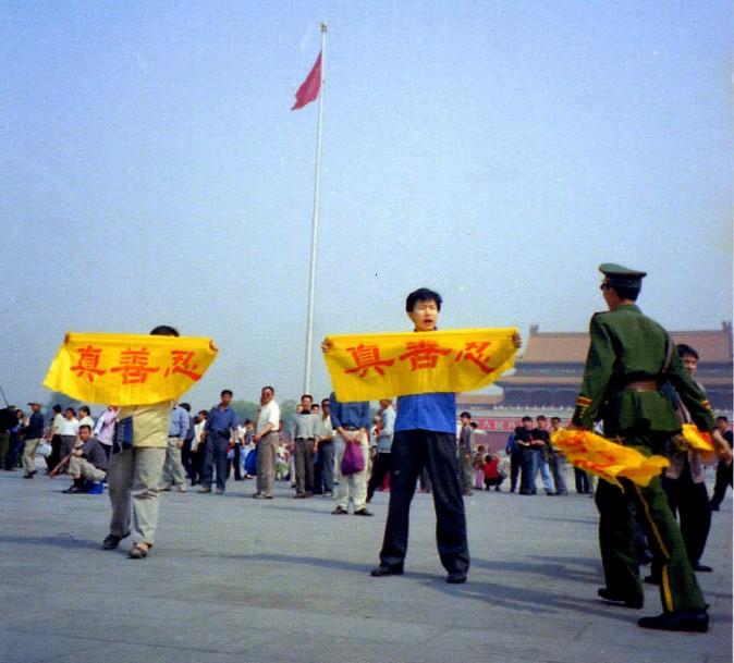 Policial chinês aborda praticantes do Falun Gong que viajaram pela China até a Praça Tiananmen para fazer apelos pacíficos contra a perseguição em 2001 (Cortesia de Minghui)