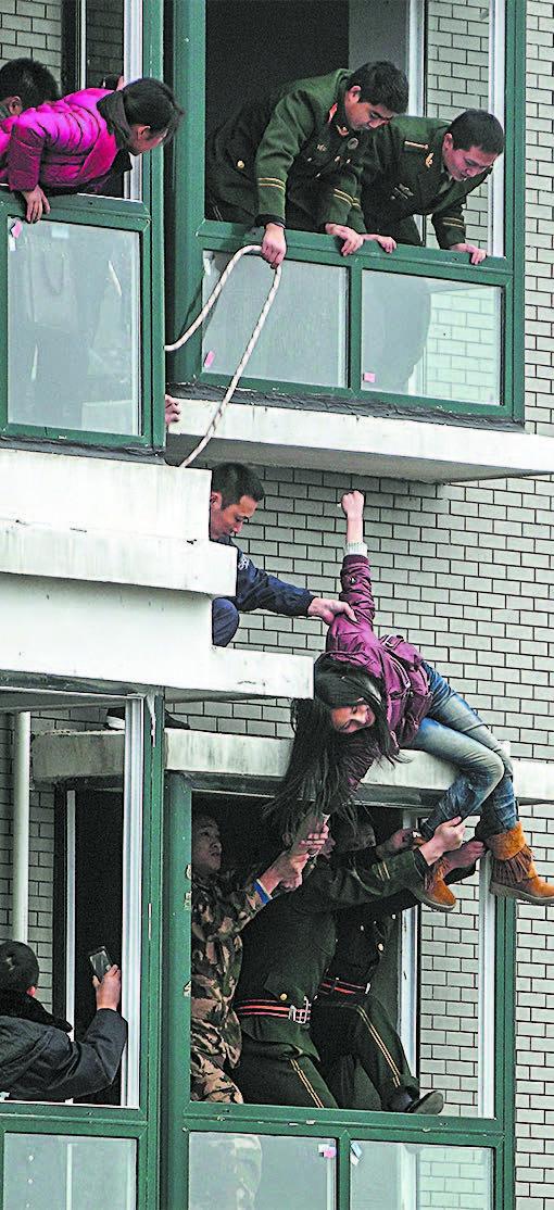 Uma mulher chinesa que tentou pular do 33º andar de um prédio em Changsha, na província chinesa de Hunan, em 28 de fevereiro de 2012 (STR/AFP/Getty Images)