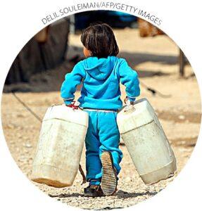 Uma garota carrega tanques de água em um campo de refugiados na província de Hasakah, na Síria, em 25 de outubro.