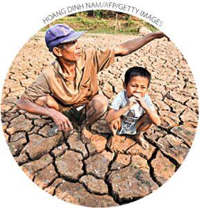 Um fazendeiro e seu filho sentam-se em seus campos de arroz atingidos pela seca no rio Mekong, fora de Vientiane, Laos, em 27 de março de 2010. Uma severa seca na região fez com que o Mekong caísse para o nível mais baixo em 50 anos.