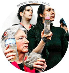 Residentes de Flint com garrafas de água contaminada e uma mecha de cabelo durante uma audiência no Capitólio em 3 de fevereiro.