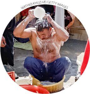 Khalid Suheil toma banho fora da tenda em que vive com sua família de nove membros em Bagdá em 20 de março de 2005.