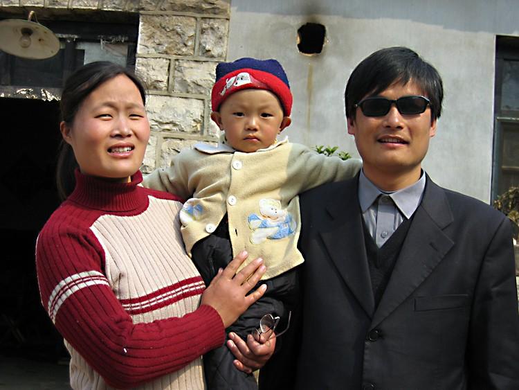 Uma foto datada de 28 de março de 2005 mostra o ativista cego Chen Guangcheng (D) com sua esposa e filho Chen Kerui fora de casa na vila de Dondshigu, província de Shandong no nordeste da China. Teng Biao ajudou a servir como advogado de Chen (STR/AFP/Imagens Getty)
