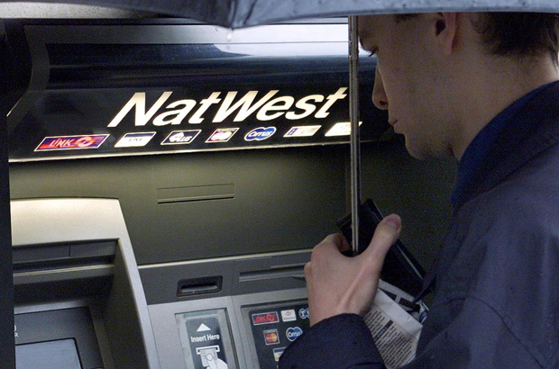 RBS, Natwest, demissões - Um homem usa um caixa eletrônico diante de uma agência do banco NatWest em The Strand, no centro de Londres (Jonathan Utz/AFP/Getty Images)